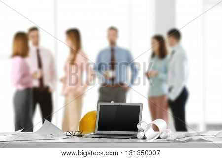 Laptop with blueprints on table and engineers on background