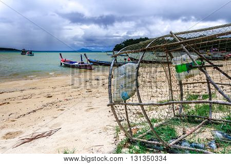 Rawai Thailand - October 27 2013: Fish trap waits on Rawai beach & traditional long-tail boats moored off-shore on southern tip of Phuket southern Thailand