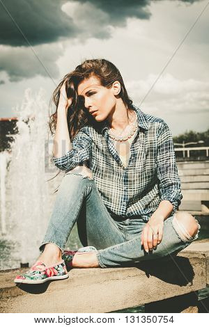 casual urban young woman sit by city fountain full body shot