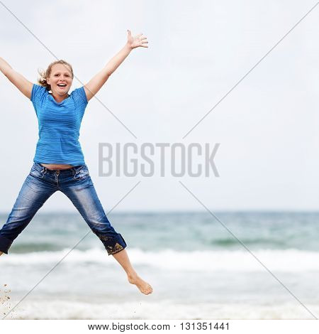 Happy young blonde woman jumping outdoors. Jumping girl. Selective focus on the models. Space for text.