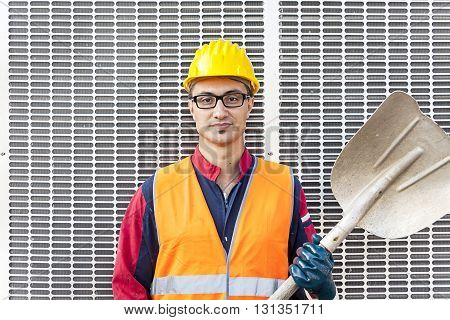Portrait Of A Young Engineer Wearing A Helmet Against Metal Background