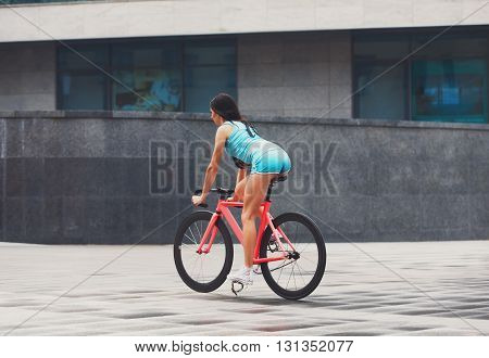 Sexy girl with bicycle. Young slim sexy sporty woman in blue shorts and white snickers long-haired, sensual posing with pink fix bicycle in urban city environment. Soft toned. Shaped buttocks.