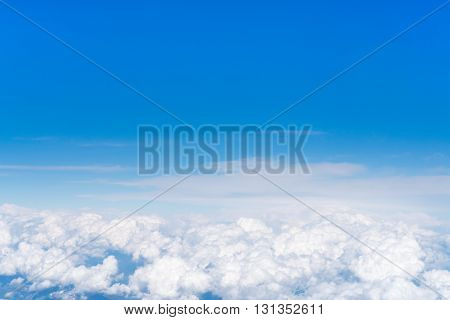 Blue sky above white fluffy cloud cloudscape background with copy space