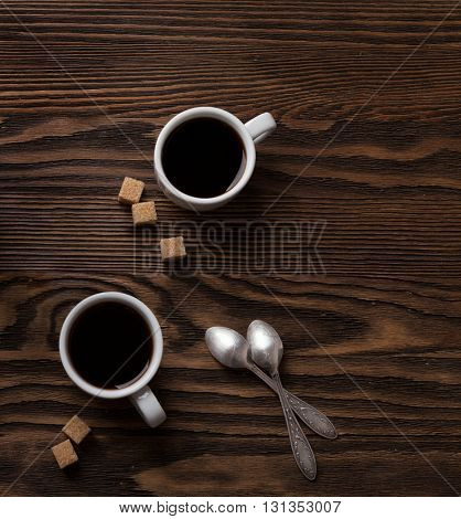 Two cups of black coffee  with pieces of cane sugar  on wooden table.