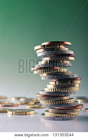Euro money closeup coins,stacked on each other in different positions background green.