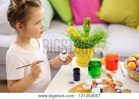 Little girl decorating Easter egg indoors