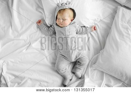 Little baby boy in grey pajamas sleeping on the bed