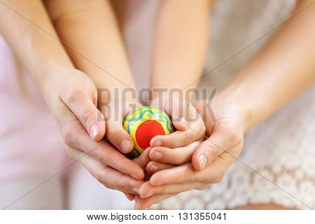 Hands of mother and daughter holding decorated Easter egg closeup