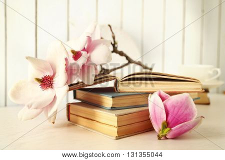 Old books with beautiful flowers on table