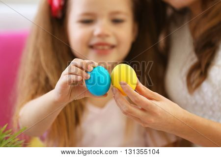 Mother and daughter holding Easter eggs closeup