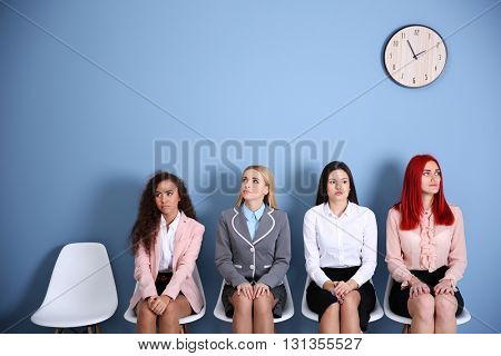 Young businesswomen sitting on a chair in blue hall