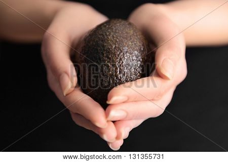 Female hands holding avocado on black background