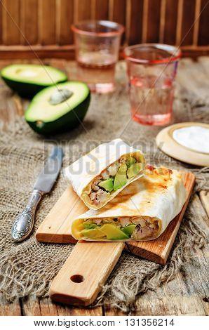 healthy chicken avocado burritos on wooden background