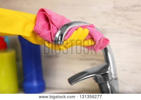Female hand with rag cleaning a tap in the kitchen