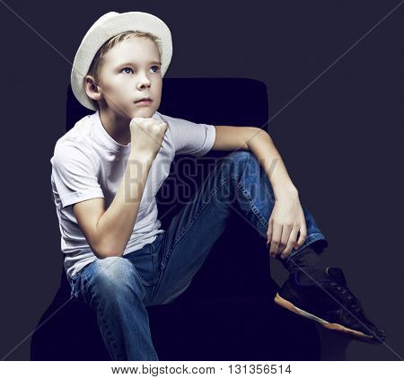 nine years old boy wearing a hat, against dark studio background