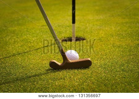 Golf putter on the green near the goal