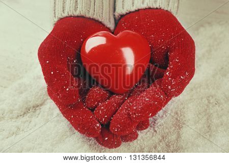 Hands in warm red gloves holding heart on snowy background