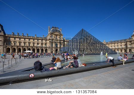 PARIS FRANCE - CIRCA JUNE 2014: Tourists in the Louvre's central courtyards with the Louvre pyramid and palace. The Louvre is the world's most visited museum