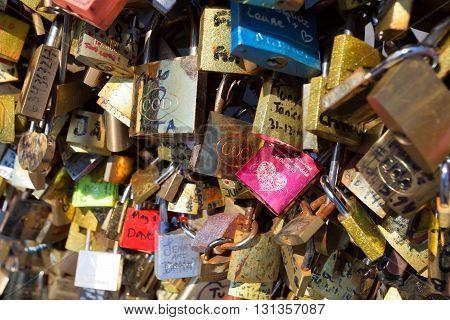 PARIS - JUNE 8 2014: Love Padlocks at Pont des Arts on June 8 2014 in Paris France. Lots of colorful locks on a bridge symbolize eternal love.