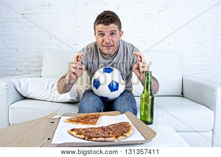 young man alone in stress watching football game on television sitting at home living room sofa couch with ball pizza box and beer bottle enjoying the match crossing fingers excited