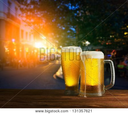 excellent light beer on a wooden table against the background of the city