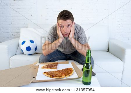 young soccer fan in stress watching football game on television sitting at home living room sofa couch with pizza box and beer bottle enjoying the match looking nervous and excited
