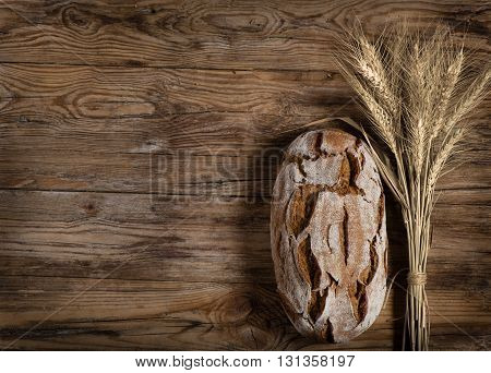 Rustic bread and ears of wheat on an old wooden table background with free text space.