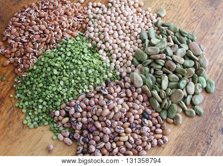 Piles of dried beans and peas on a rustic wooden table top