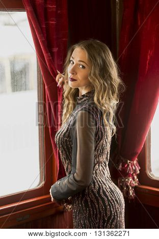 Toned portrait of sexy woman in vintage dress looking out of window in train