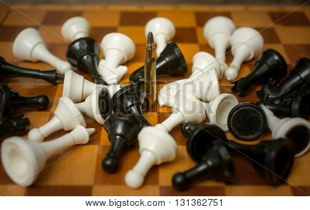 Conceptual photo of weapon power. One bullet among lying chess pieces