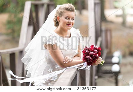 Portrait of beautiful bride with red bouquet posing on bridge at windy day