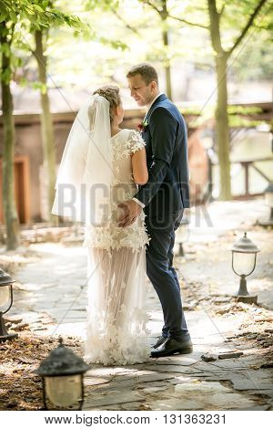 Beautiful newly married couple walking at sunny park