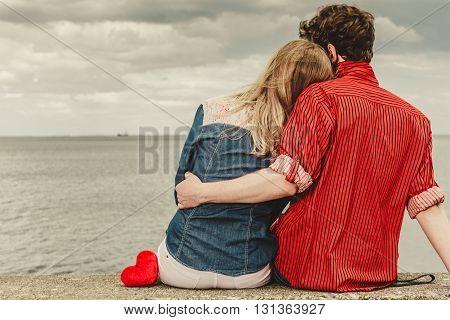 Couple Sitting Hugged On Sea Shore