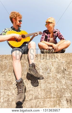 Young man hipster playing guitar for woman. Handsome guy and pretty girl in sunglasses relaxing on summer vacation.