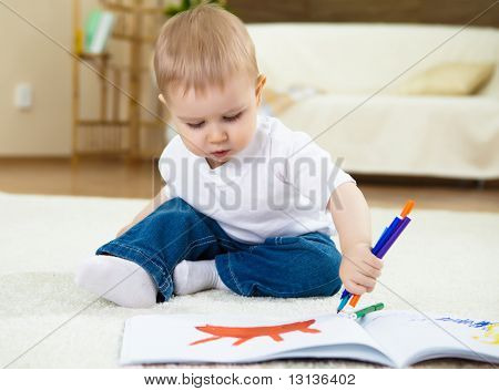 little boy drawing with color pencils