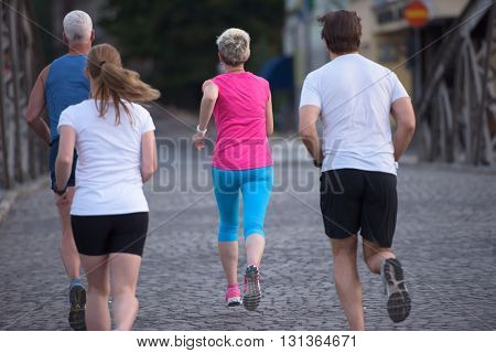 people group jogging  runners team on morning  training workout with sunrise in background
