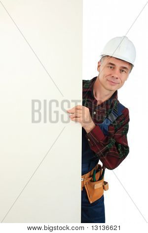 Muscular professional man in a builder uniform with board.