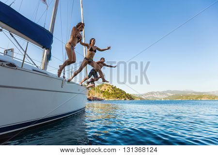 Group of young friends jumping from the yacht into sea