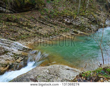 Mountain Stream in Springtime. Cascade river over mossy rocks.