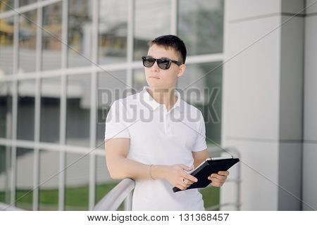 Portrait of a young businessman keeping tablet pc on the street. Man with dark sunglasses and white polo.