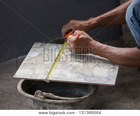 Ceramic Tile Being Measured With A Tape Measure