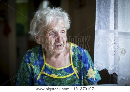 An elderly woman (80+) sitting in the house near the window.