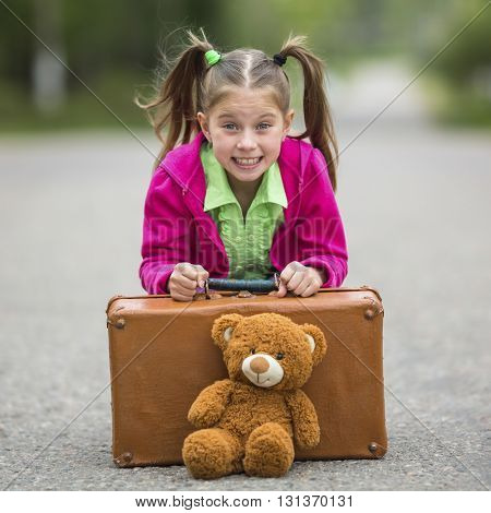 Little cute girl on the road with a suitcase and a Teddy bear.