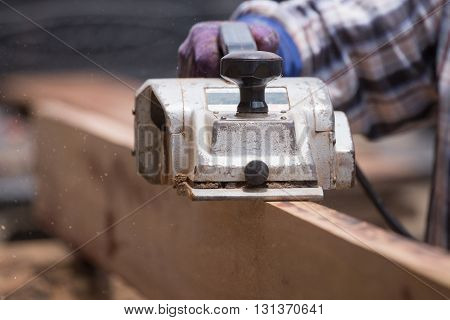 Worker Planing A Wood With A Electric Plane