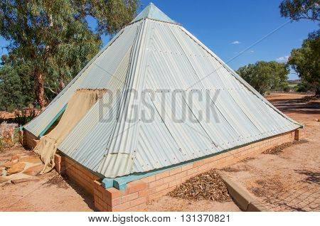 Pyramid shaped building structure exterior with metal roofing and brick base surrounded by sand and trees under a blue sky.