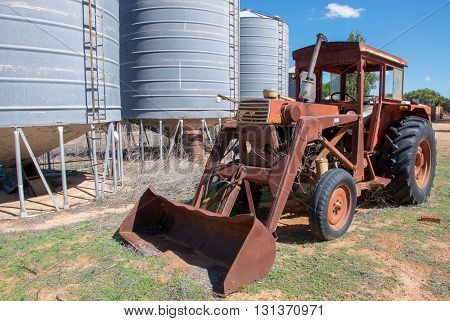 Old rusted antique tractor with large wheels and bucket in front of three silos on farmland with generic vegetation under a blue sky in Western Australia.