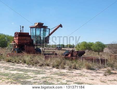 Old rusted combine farm machinery in a sandy, vegetated farmland landscape under a blue sky in Western Australia.