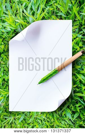Close up note paper and pen on grass background. eco concepts