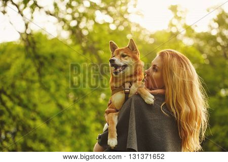 poster of Girl and dog Shiba Inu hug in a spring park. Walking with a pet. Pedigree dog. Walking dogs. Dog happiness.