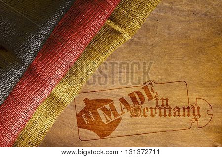 Flag of Germany with a stylized imprint on the wooden background Made in Germany.